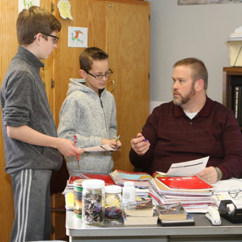 Teacher talking to two students