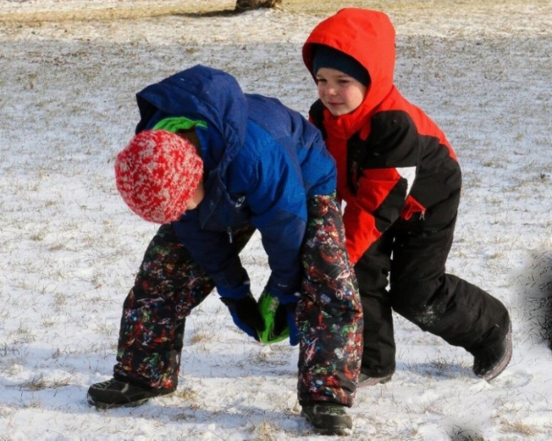 Boys playing football in snow