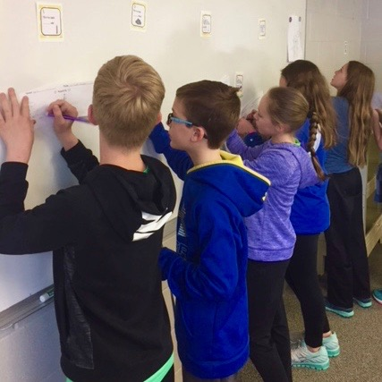 Students copying words at board