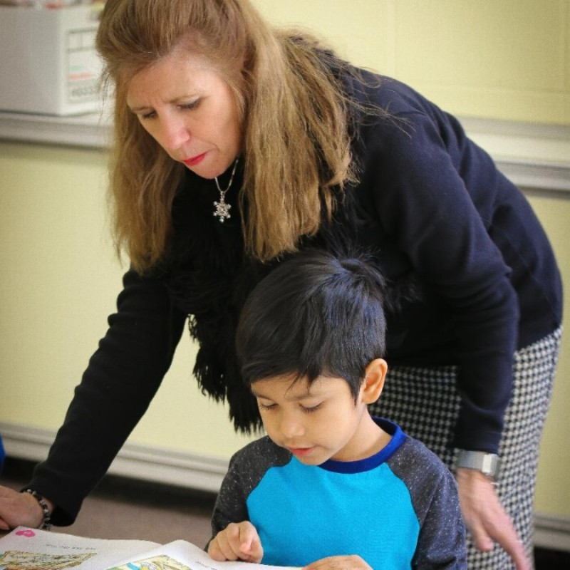 Kindergarten teacher helping boy read