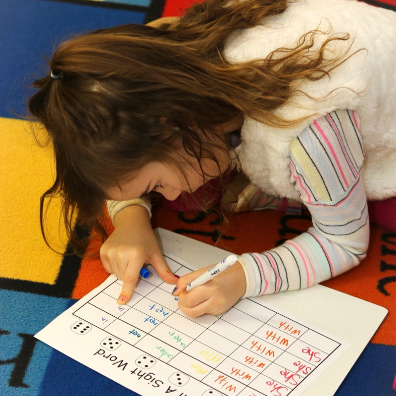 Kindergarten girl writing numbers