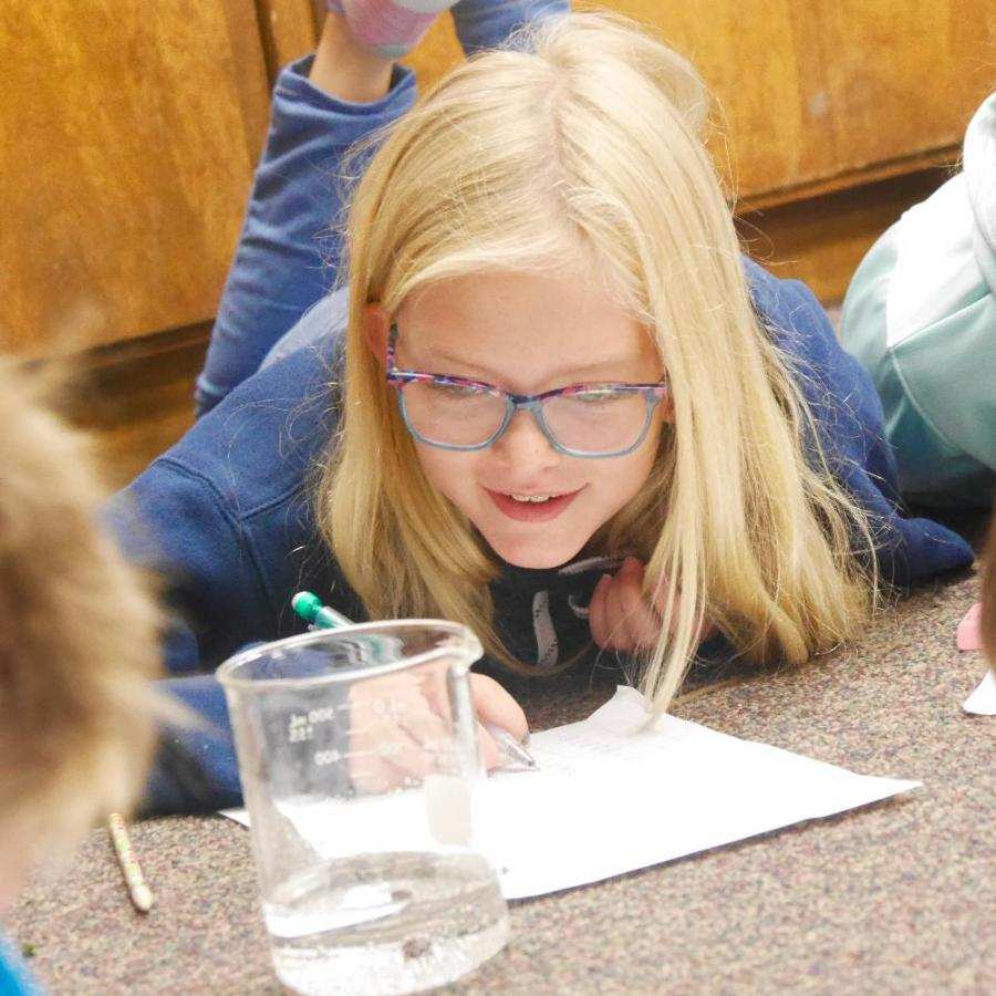 Girl looking at science beaker