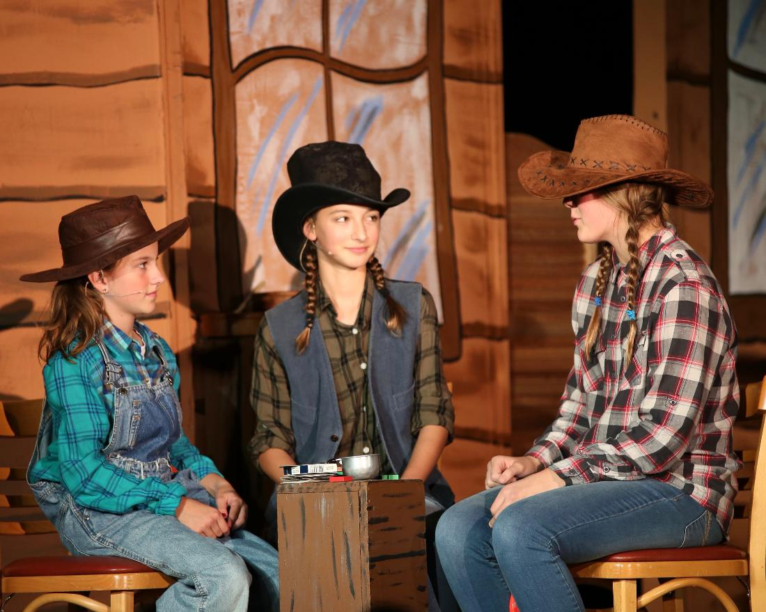 Girls acting in play on stage