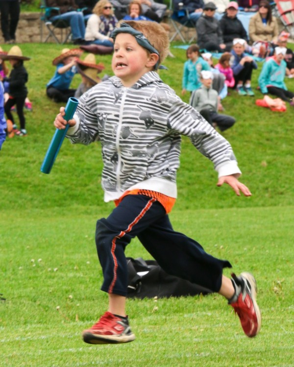 Young boy running with relay baton