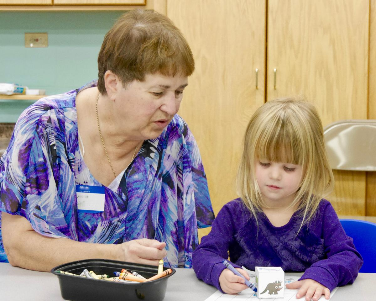 Preschool girl coloring with grandma