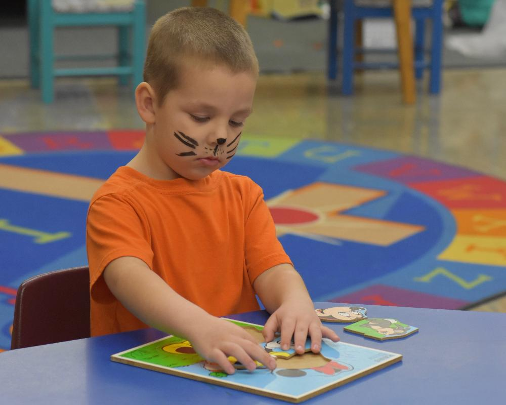 Preschool boy doing puzzle